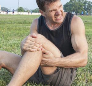 man holding knee in sports injury