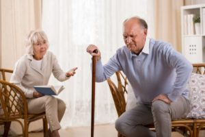 man with arthritis having trouble standing up